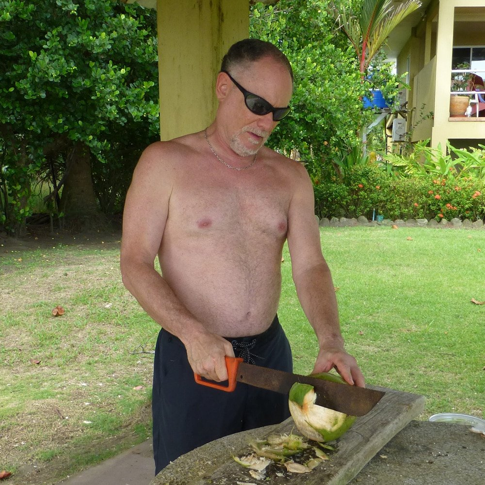 slicing open a young coconut with a machete in Costa Rica