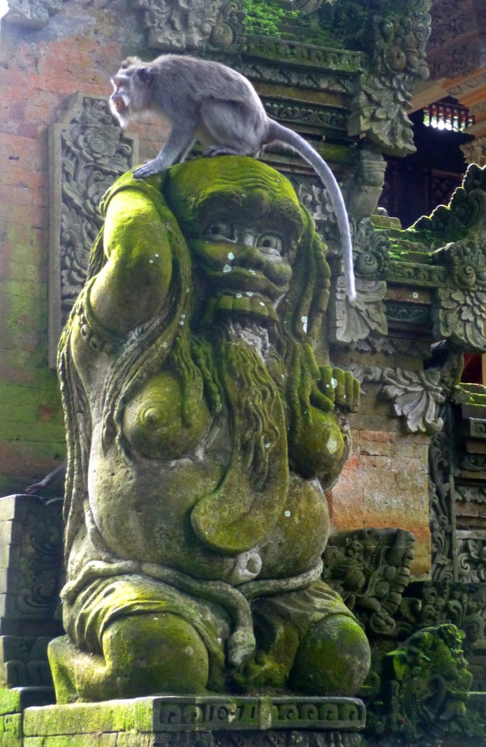Monkey on statue in Sacred Monkey Forest, Bali