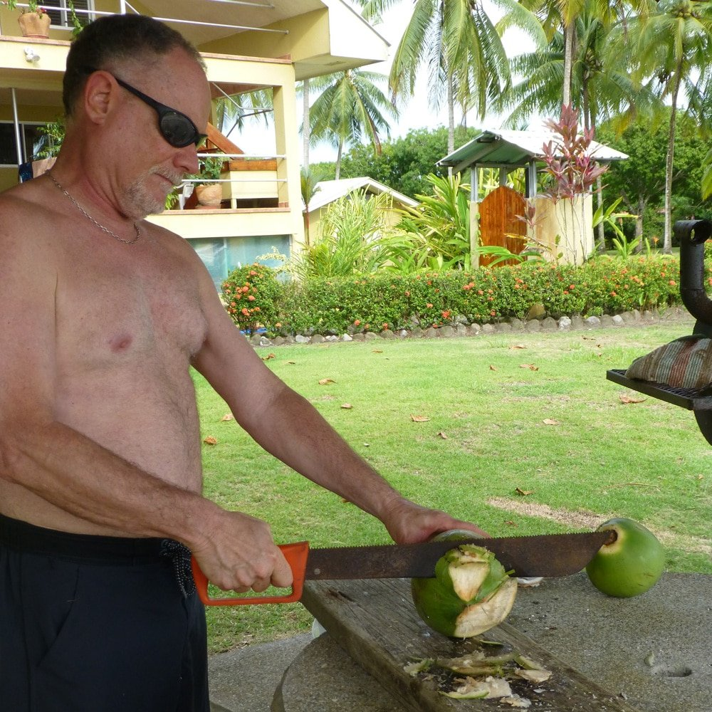 Cutting open a young coconut with a machete